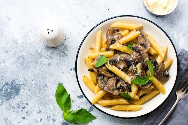 버섯, 파마산 치즈, 바질 잎을 곁들인 펜네 리가테 파스타는 밝은 오래된 콘크리트 배경의 세라믹 접시에 있습니다. 선택적 초점