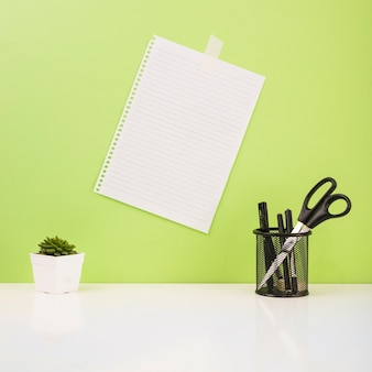 Pens and scissors in holder near paper stucked on green wall