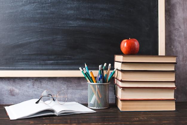 칠판의 배경에 대해 테이블에 펜, 사과, 연필, 책 및 안경