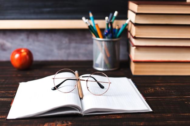 Ручки, яблоко, карандаши, книги и очки на столе, на фоне классной доски