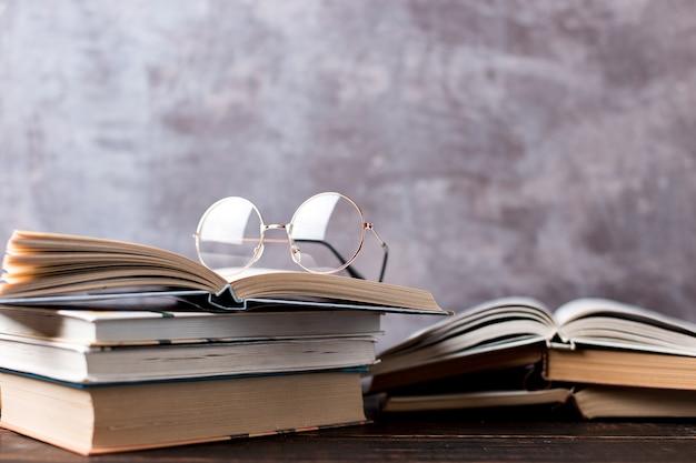 Ручки, яблоко, карандаши, книги и очки на столе