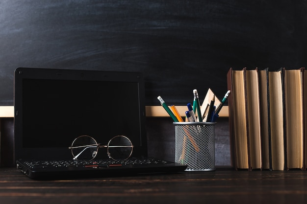 Pens, apple, pencils, books, laptop and glasses on the table, on chalkboard background