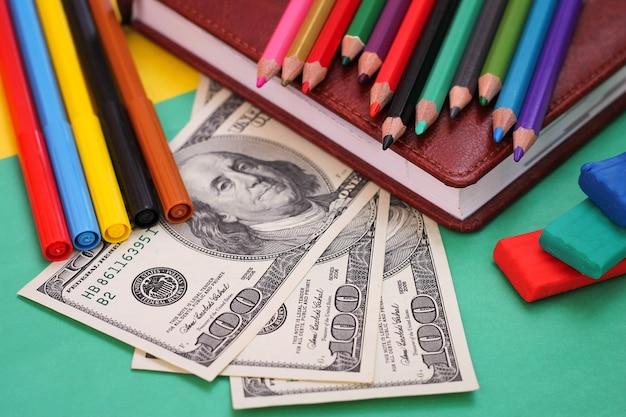Ручки, цветные карандаши, пластилин, книга, стодолларовые купюры