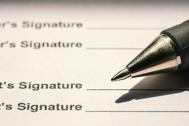 Pens and contract documents are placed on the desk.