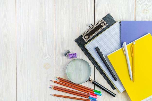 Ручки, тетради, точилки для карандашей на белом фоне, вид сверху копией пространства