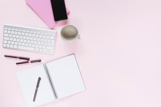 Ручки на спиральном ноутбуке с мобильным телефоном и клавиатурой на розовом фоне