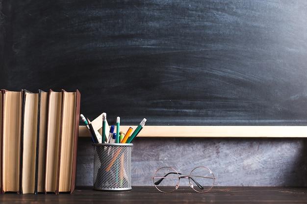 Ручки, карандаши, книги и очки на столе на фоне классной доски
