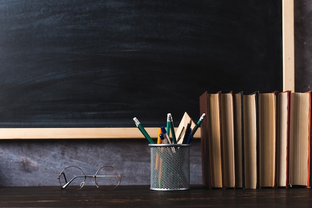 Pens, pencils, books and glasses on the table, against the background of a chalkboard