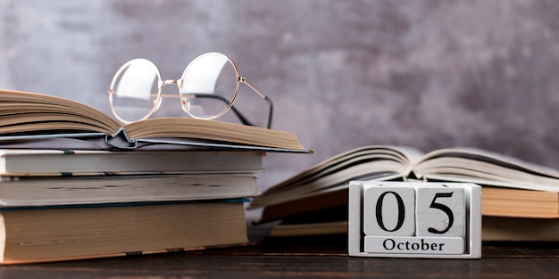 Pens, pencils, books and glasses on the table. calendar october 5, copy space.
