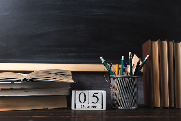 Pens, pencils, books and glasses on the table, on chalkboard background. calendar october 5, copy space.