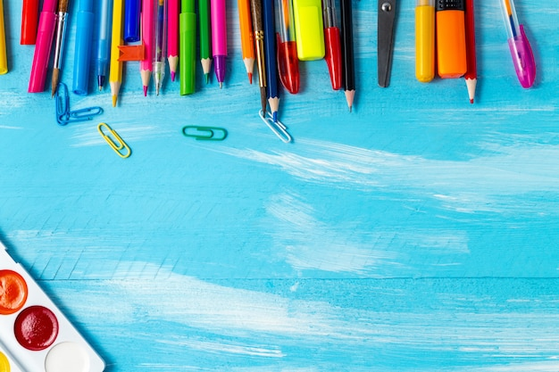 Pens, pencils, brushes, felt pens, markers, paper clips, watercolors background. back to school concept