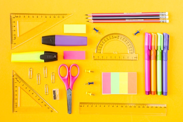 Pens, pencils markers, buttons, paperclips and rulers on a yellow background