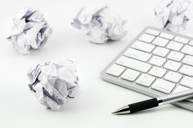 Pens placed on computer keyboard and wrinkled paper balls on a white table