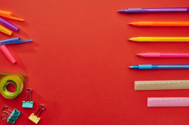 ペン、定規、ペーパークリップ、赤い背景。オフィスの文房具、学校や教育の付属品、書き込みおよび描画ツール