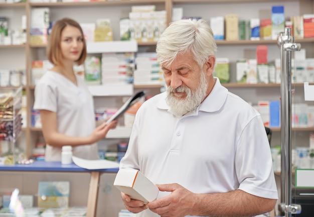 Пенсионер выбирает лекарство в аптеке.