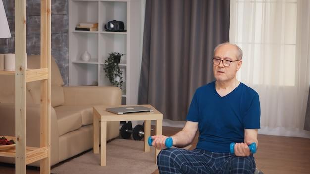 居間でバランスボールの上腕二頭筋トレーニングをしている年金受給者。老人年金受給者が自宅でヘルスケアスポーツを健康的に訓練し、高齢者でフィットネス活動を行う