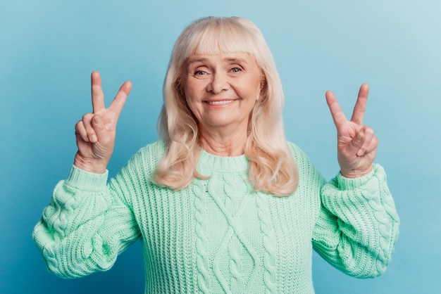 Pensioner lovely woman show two v-sign isolated blue background