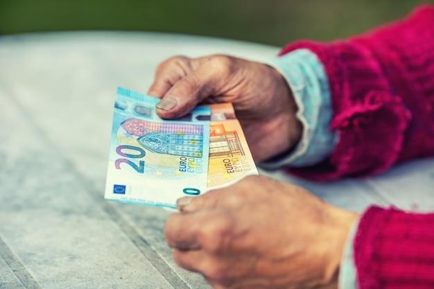 손에 유로 지폐를 들고 연금 남자입니다.