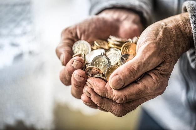 손에 유로 동전을 들고 연금 남자입니다. 낮은 연금의 테마.