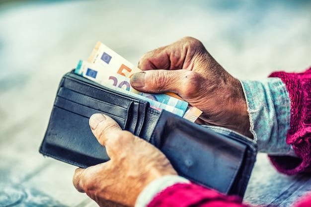 돈으로 손 지갑에 들고 연금 남자입니다.