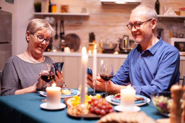 電話を使って笑って、夕食の時間に台所で妻と会話している年金受給者の男性。食堂のテーブルに座って、ブラウジング、検索、電話、インターネット、