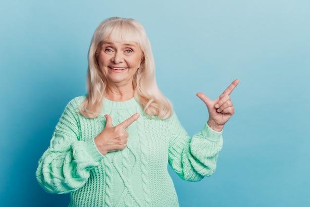 연금 노인 여성 발기인 포인트 손가락 복사 공간 파란색 배경에 고립