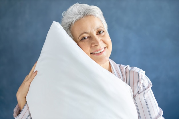 Пенсионерка позирует и обнимает белую мягкую подушку