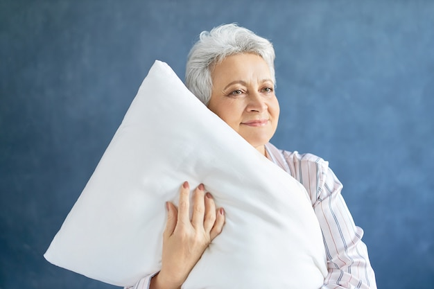 Pensioner posing and hugging white soft pillow