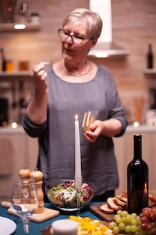 夫とのお祝いの夕食の準備をしている年金受給者。夫がロマンチックな夕食を待っている年配の女性。結婚記念日の食事を準備する成熟した妻。