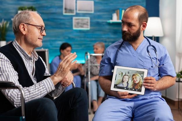 オンラインビデオ通話中にリモートの友人に挨拶する年金受給者のシニア男性