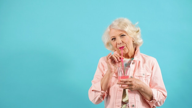 Pensioner in stylish clothes enjoys a drink
