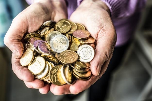 손에 유로 동전을 들고 연금 여자입니다. 낮은 연금의 테마.