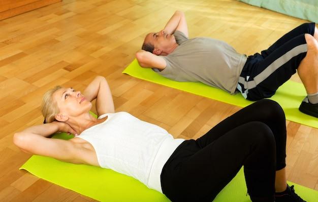 Пенсионеры делают упражнения в закрытом помещении