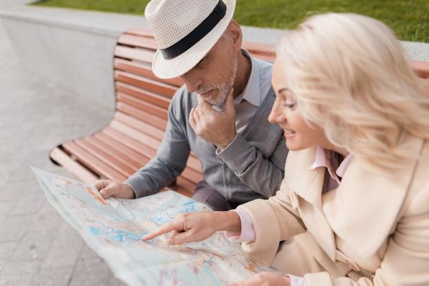 연금 수급자는 벤치에 앉아 도시의지도를 연구합니다.