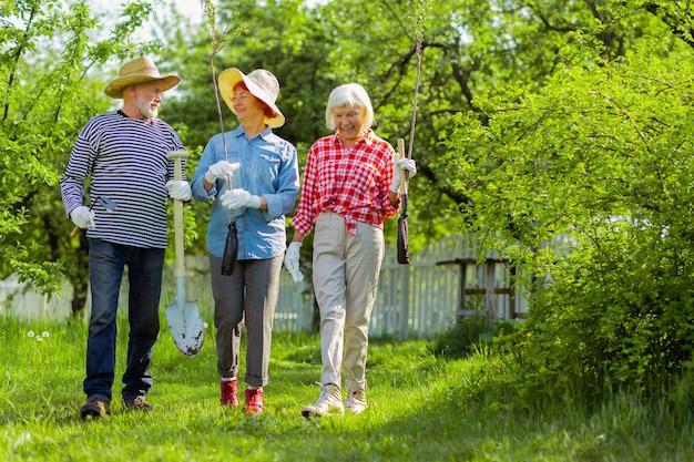 Пенсионеры гуляют. сияющие пенсионеры ходят с прядями и лопатами перед тем, как сажать их возле домов