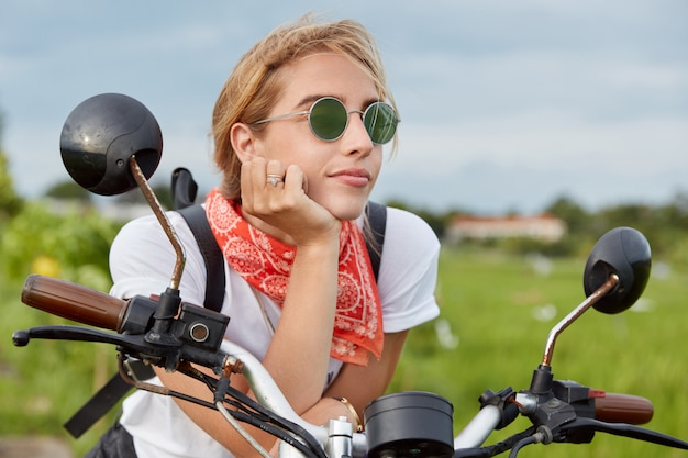 Pensive active woman looks with thoughtful expression into distance while sits on motorbike, takes break after long driving, poses on transport outdoor, enjoys high speed and wonderful nature