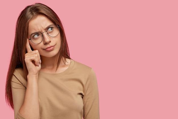 Una femmina adorabile pensierosa tiene il dito sulla tempia, essendo immersa nei pensieri, ha una faccia seria, ricorda qualcosa, posa contro il muro rosa