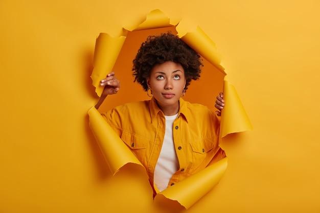 物思いにふける愛らしい女性は、上向きに視線を保ち、破れた紙の穴に立って、ファッショナブルな服を着て、何かについて考えます