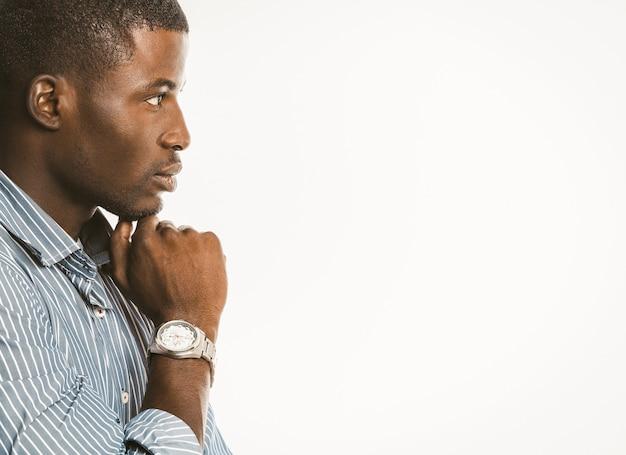 物思いにふけるアフリカ系アメリカ人のビジネスマンは、高級腕時計で彼のあごに手で触れます。