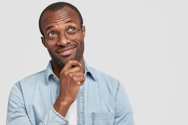 Pensive african american holds chin and looks happily upwards
