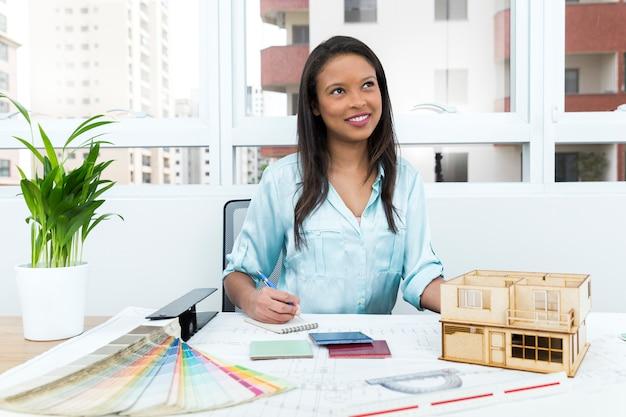 Задумчивая афроамериканская леди на стуле, делающая заметки около плана и модели дома на столе