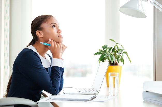 オフィスの職場に座っているドレスを着た物思いにふけるアフリカのビジネス女性。