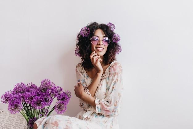 目をそらしている紫色の花を持つ物思いにふけるアフリカの女の子。孤立したデボネア黒人女性の屋内ショット。