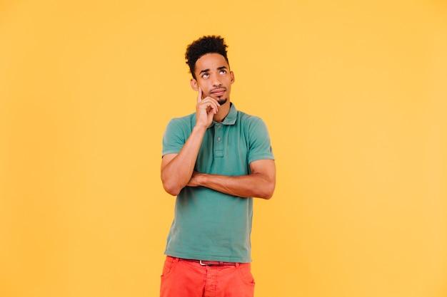 짧은 머리를 찾는 잠겨있는 아프리카 남자. 녹색 티셔츠에 진정 흑인 남성 모델의 실내 사진.