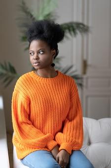 物思いにふけるアフリカの千年紀の女性は、ソファに座って、考えて、窓を見ながらオレンジ色のセーターを着ています。