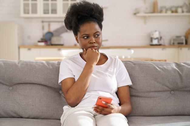 物思いにふけるアフリカの女性が携帯電話を持って、人間関係の問題について考え、目をそらして熟考する