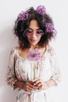 紫の花でポーズをとって物思いにふけるアフリカの若い女性。ネギとメガネでリラックスした黒人の女の子。