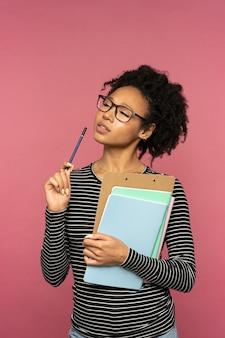 Задумчивая афро-американская учительница изолирована на розовой стене
