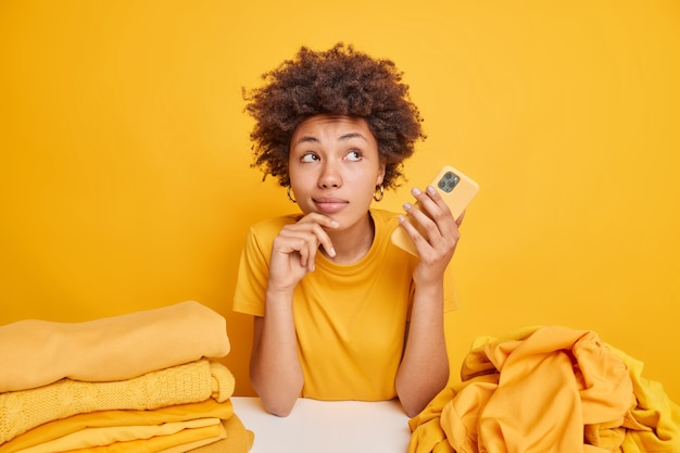 Pensive afro american woman has dreamy expression holds modern mobile phone sits at table with piles of clothes isolated over yellow wall busy folding laundry. clothing and housekeeping
