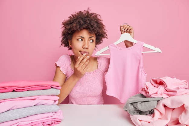 Pensive afro american woman holds shirt on hanger looks away with thoughtful expression sits at table with piles of unfolded clothing isolated over pink